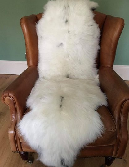 Double natural rare breed Sheepskin on a leather chair