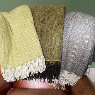Pure Wool Herringbone Throws in Lime, Lime-Brown, Brown-Green tweed on a leather chair