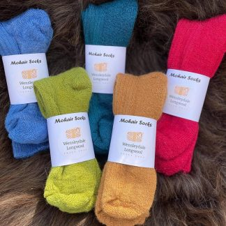 Sheep Shop Mohair socks in various colours on a sheepskin in the sunshine