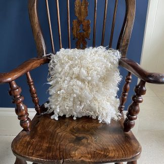 Wensleydale Shearling Fleece cushion on wooden chair
